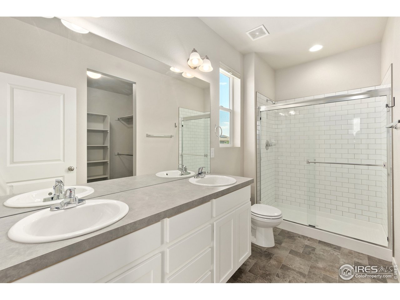 Four piece primary bathroom with walk-in shower, tile surround, and large walk-in closet
