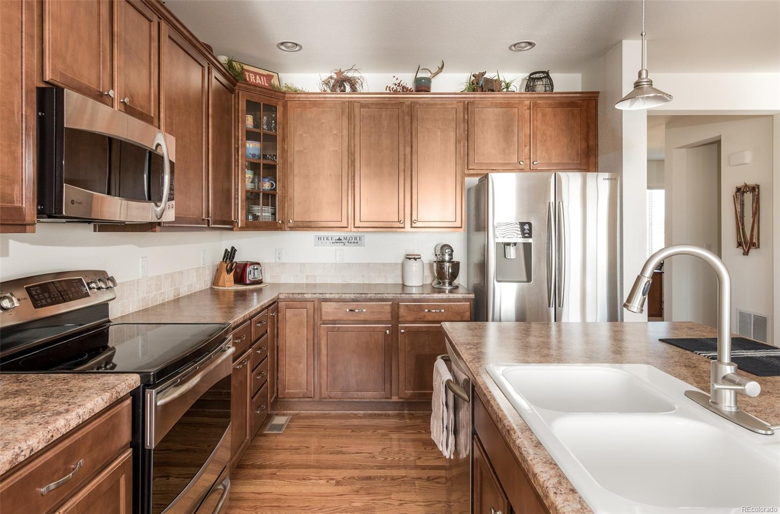 Large kitchen with plenty of storage space and crown moulding on tall cabinets.