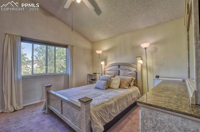 Master bedroom with vaulted ceilings, fan & mountain views