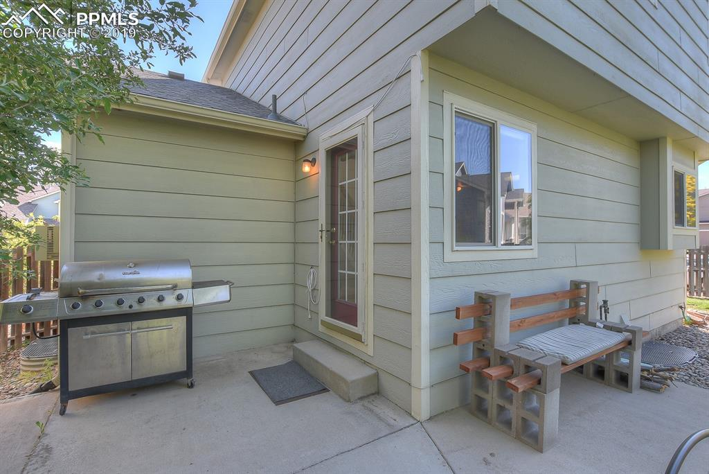 Back door and patio perfect for grilling & the bench stays