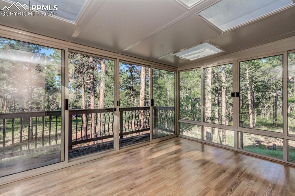 Sunroom provides additional living space.  Open the screened doors and windows and enjoy the breeze.