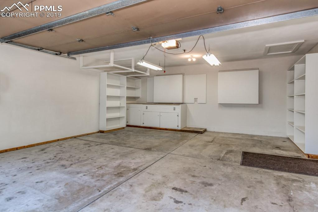 Garage features car charger outlet, storage and work space.