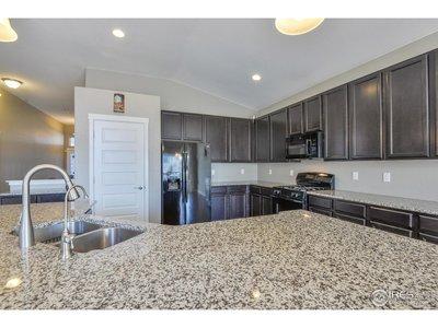 Slab Granite Island and Espresso Cabinetry