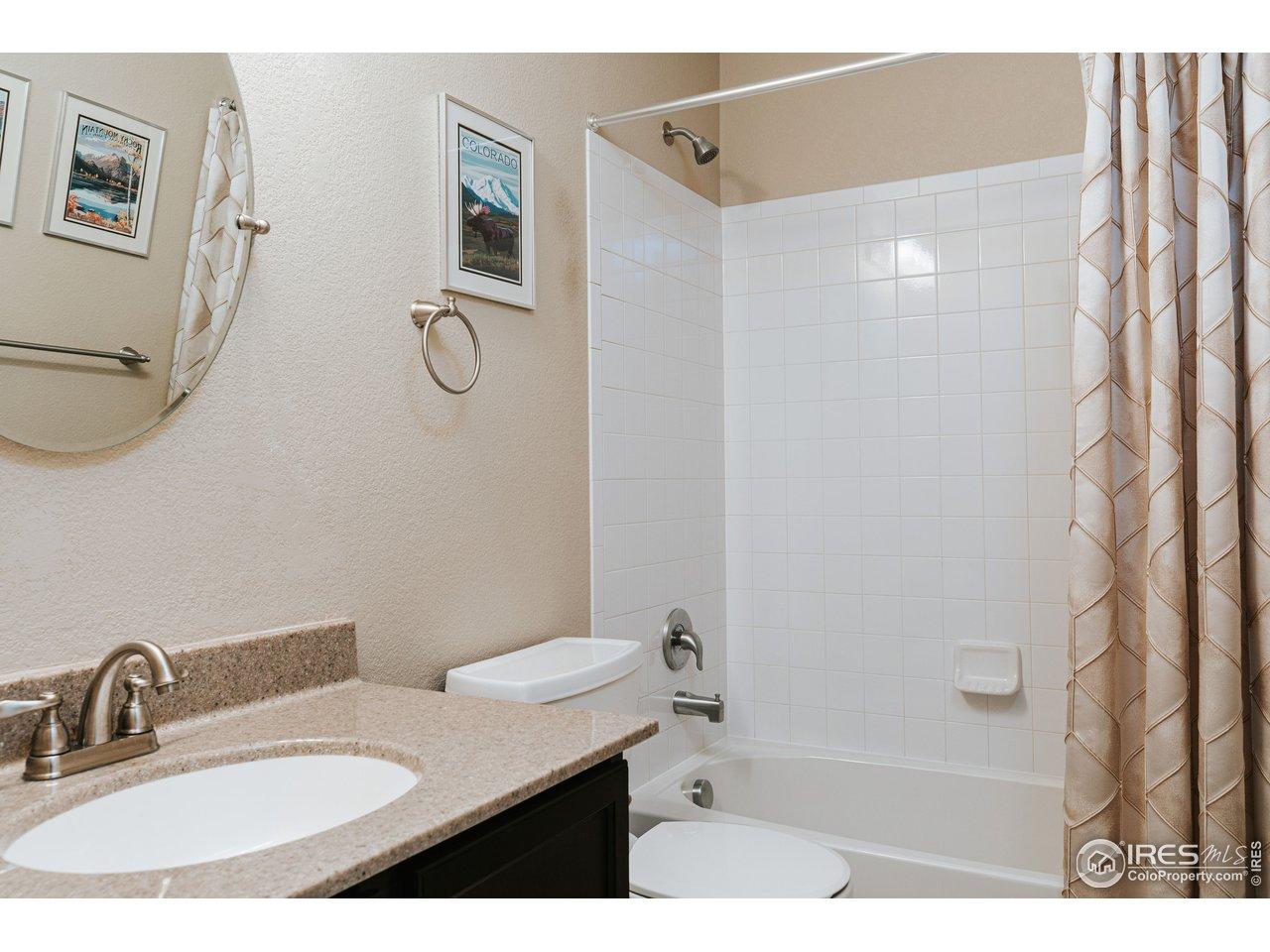 Main bath w/ tiled floors & granite vanity