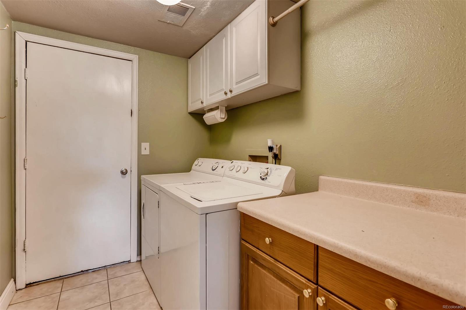 Laundry room with cabinets. Washer and dryer stays.