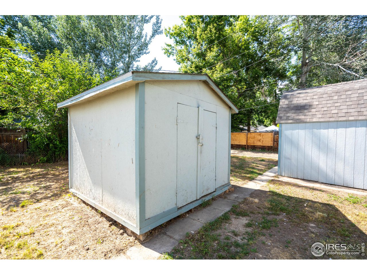 Large shed with loft storage and concrete flooring.