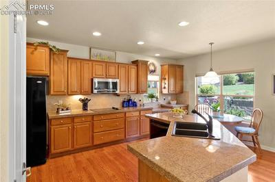 Beautiful maple cabinetry with large island, granite-tile counters and hardwood floors.