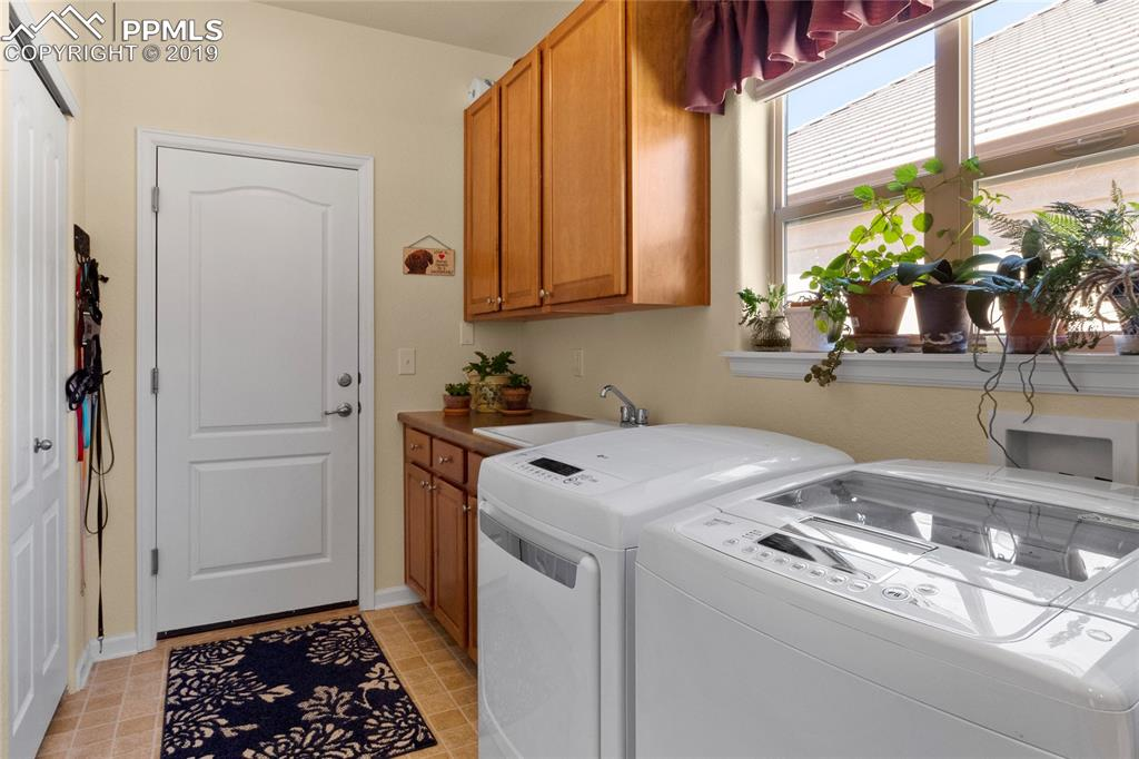 Sunny laundry room features double closets, additional cabinetry and sink. Washer and dryer included.
