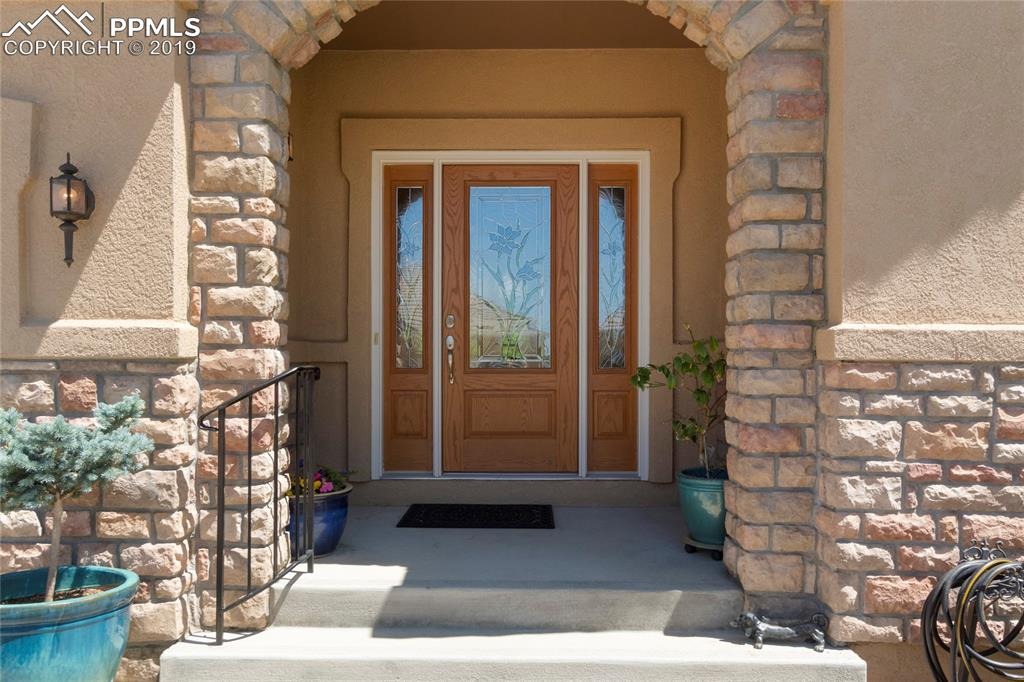 Graceful stone-arched entry with custom leaded-glass doors.