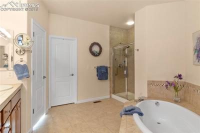 Garden tub, stand-up shower, ceramic tile. Walk-in closet features custom-designed cabinetry.