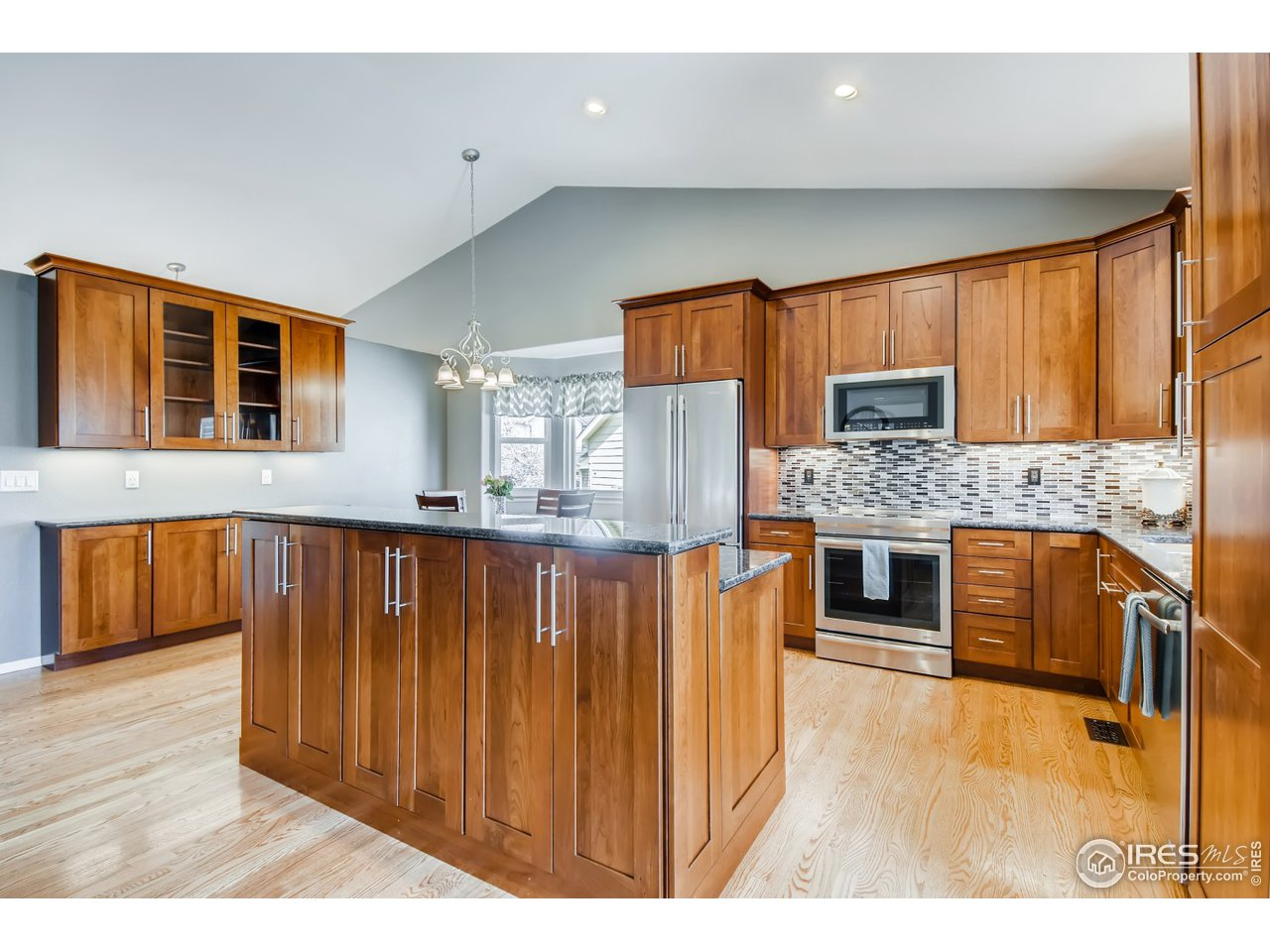 Custom kitchen loaded with extras. Cherry cabinets, soft close doors, sliding utensil racks, swing out pantry racks, induction stove, convection microwave, Jenn Air SS appl. custom backsplash, under cab lighting and refinished wood floors.
